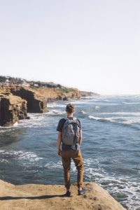 boy on cliff with backpack